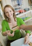 Mujer joven que paga ropa con la tarjeta de crédito Imagen de archivo