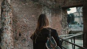 Mujer joven que pasa a través de Roman Forum en Roma, Italia La muchacha está capturando la belleza de paredes viejas y está disf metrajes