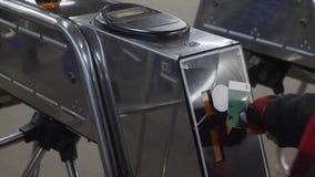 Mujer joven que pasa a través de un torniquete con la tarjeta electrónica del acceso en cierre subterráneo del metro para arriba almacen de video