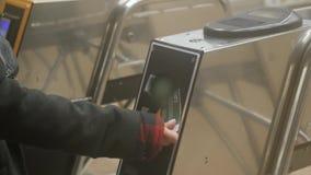 Mujer joven que pasa a trav?s de un torniquete con la tarjeta electr?nica del acceso en cierre subterr?neo del metro para arriba metrajes
