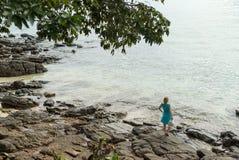 Mujer joven que permanece en la playa rocosa Imágenes de archivo libres de regalías