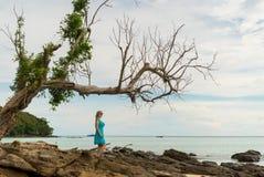 Mujer joven que permanece en la playa rocosa Imagenes de archivo