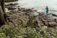 Mujer joven que permanece en la playa rocosa Foto de archivo libre de regalías
