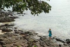 Mujer joven que permanece en la playa rocosa Imagen de archivo libre de regalías