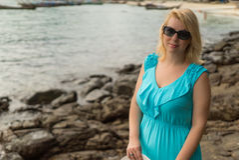 Mujer joven que permanece en la playa rocosa Fotos de archivo libres de regalías