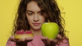 Mujer joven que pesa la manzana y la torta en manos en estudio amarillo metrajes
