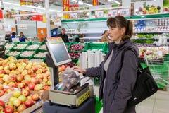 Mujer joven que pesa las patatas en escalas electrónicas Imagen de archivo