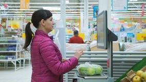 Mujer joven que pesa manzanas en escalas electrónicas almacen de video
