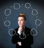 Mujer joven que piensa con la circulación de la nube alrededor de su cabeza Fotografía de archivo libre de regalías