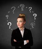 Mujer joven que piensa con la circulación del signo de interrogación alrededor de su h Foto de archivo