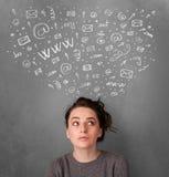 Mujer joven que piensa con los iconos sociales de la red sobre su cabeza Imágenes de archivo libres de regalías