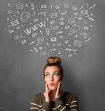 Mujer joven que piensa con los iconos sociales de la red sobre su cabeza Foto de archivo libre de regalías