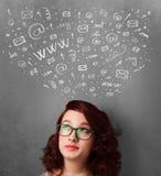 Mujer joven que piensa con los iconos sociales de la red sobre su cabeza Imagen de archivo libre de regalías