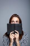 Mujer joven que piensa detrás de su diario Fotos de archivo