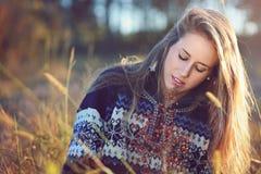 Mujer joven que piensa en prado del otoño Fotografía de archivo