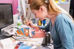 Mujer joven que pinta a Clay Mask Foto de archivo