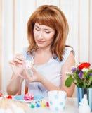 Mujer joven que pinta los huevos de Pascua Foto de archivo