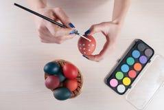 Mujer joven que pinta los huevos de Pascua con el cepillo imagen de archivo libre de regalías