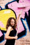 Mujer joven que pinta una pared con la pintada Imágenes de archivo libres de regalías