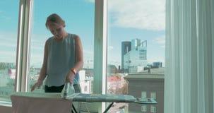 Mujer joven que plancha la ropa por la ventana en casa almacen de metraje de vídeo
