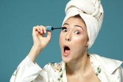 Mujer joven que pone el rimel del ojo sobre el fondo azul, tre de la belleza Imágenes de archivo libres de regalías
