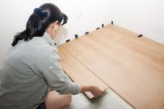 Mujer joven que pone el suelo laminado Imágenes de archivo libres de regalías