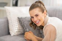 Mujer joven que pone en el sofá Imagenes de archivo