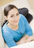 Mujer joven que pone en el sofá Imagen de archivo