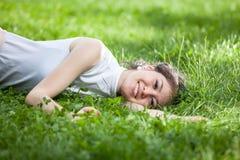 Mujer joven que pone en hierba Foto de archivo