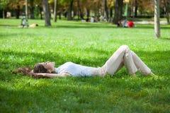 Mujer joven que pone en hierba Imágenes de archivo libres de regalías