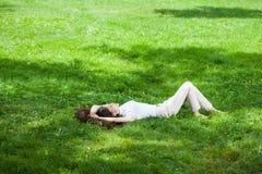 Mujer joven que pone en hierba Imagen de archivo libre de regalías