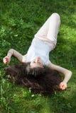 Mujer joven que pone en hierba Imagenes de archivo