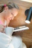 Mujer joven que pone en la cama que lee una revista Foto de archivo