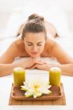 Mujer joven que pone en la tabla del masaje con las velas Fotografía de archivo libre de regalías