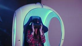 Mujer joven que pone en las auriculares de la realidad virtual que se preparan para la sesión del vr Imágenes de archivo libres de regalías