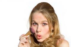 Mujer joven que pone en maquillaje Fotos de archivo