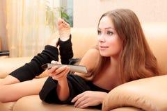 Mujer joven que pone en un sofá Imágenes de archivo libres de regalías