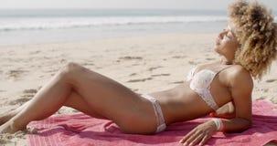 Mujer joven que pone en una playa en su bikini almacen de metraje de vídeo