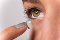 Mujer joven que pone la lente de contacto en su ojo Fotos de archivo libres de regalías