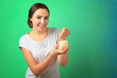 Mujer joven que pone la moneda en la hucha imagen de archivo