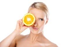 Mujer joven que pone la rebanada de limón sobre el ojo Fotos de archivo libres de regalías