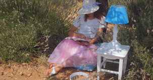 Mujer joven que pone leyendo un libro debajo del árbol almacen de video