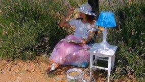 Mujer joven que pone leyendo un libro debajo del árbol almacen de metraje de vídeo