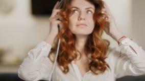 Mujer joven que pone los auriculares en la cocina moderna Muchacha del primer que disfruta de música almacen de metraje de vídeo