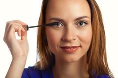 Mujer joven que pone maquillaje del rimel Fotos de archivo libres de regalías