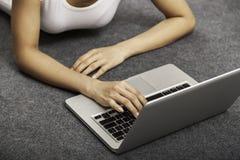 Mujer joven que pone mientras que usa el ordenador portátil Imágenes de archivo libres de regalías
