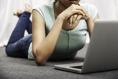 Mujer joven que pone mientras que usa el ordenador portátil Foto de archivo