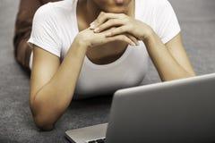 Mujer joven que pone mientras que usa el ordenador portátil Fotografía de archivo libre de regalías