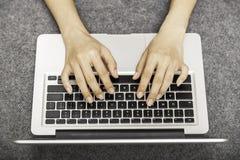 Mujer joven que pone mientras que usa el ordenador portátil Fotos de archivo libres de regalías