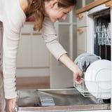 Mujer joven que pone platos en el lavaplatos Imagen de archivo libre de regalías